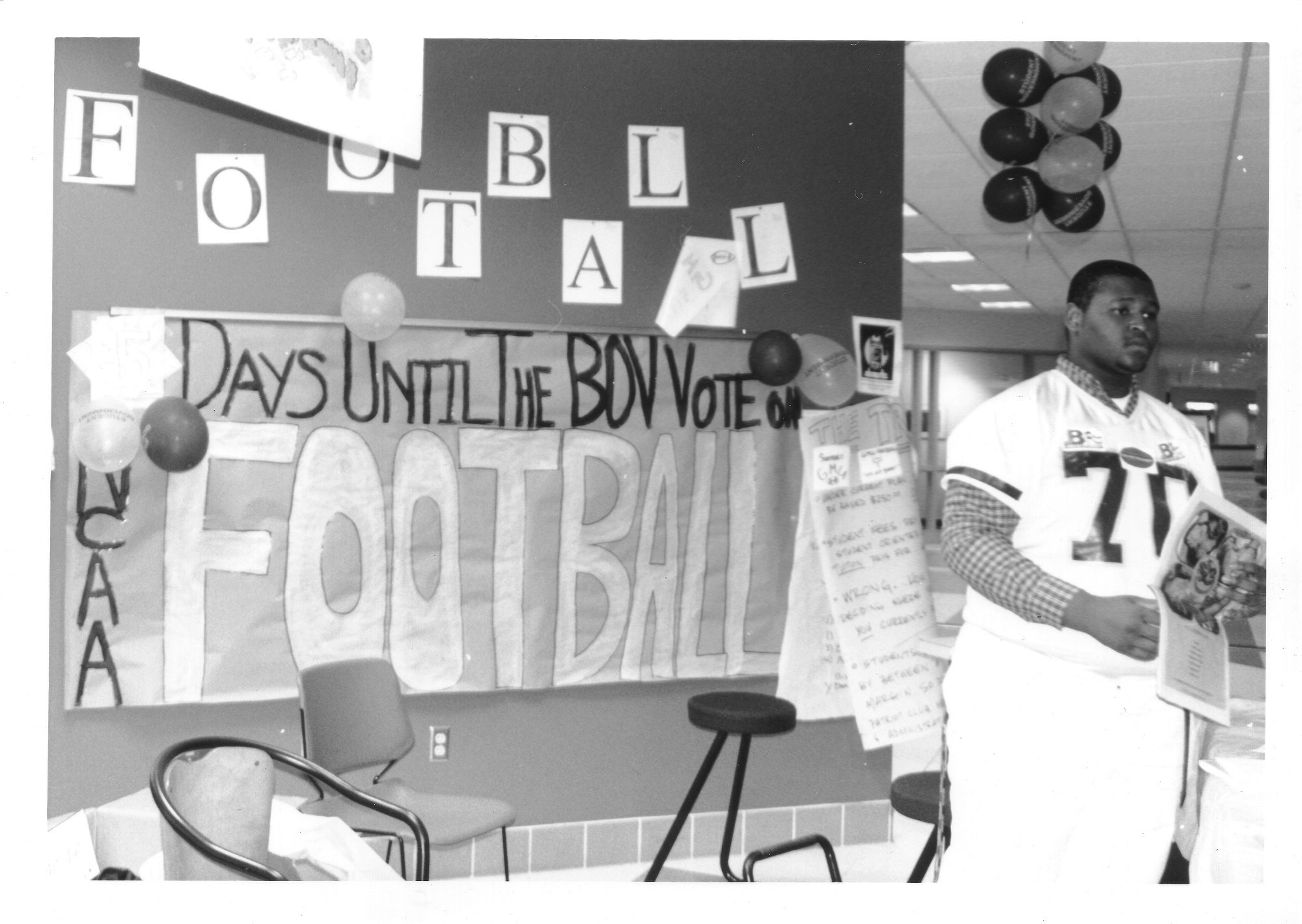 George Mason University football player stands in front of a display inside the George W. Johnson Center, 1998
