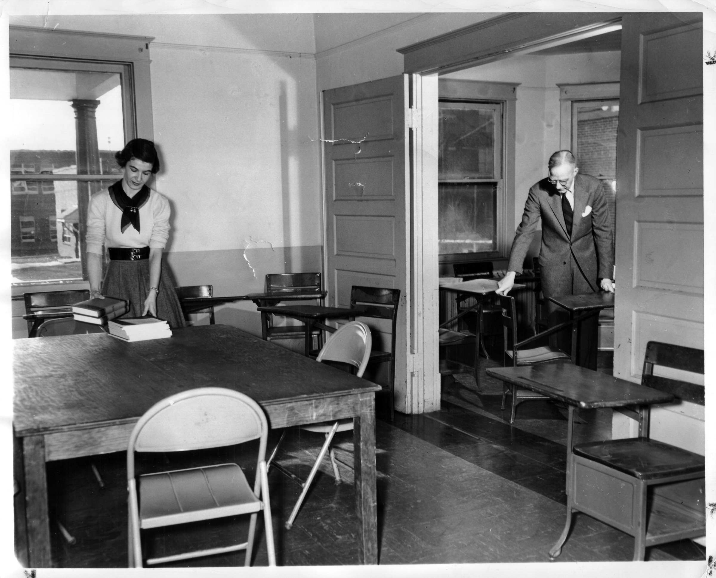John Norville Gibson Finley and assistant set up desks in a classroom, Northern Virginia University Center, December 22, 1953.